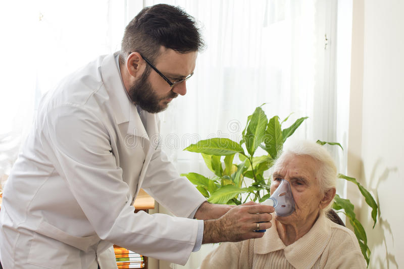 The doctor holds inhaler the face of an old woman. royalty free stock photo