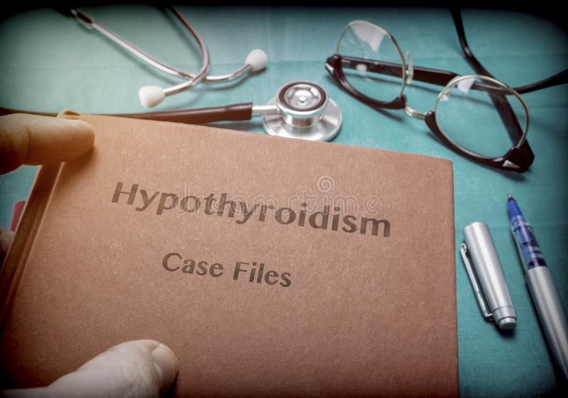 Doctor holds in its hands a book on the Hypothyroidism royalty free stock image