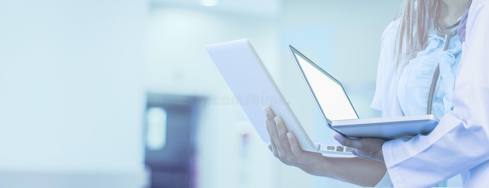 Doctor holds laptop in hand, background is hospital,for Web banner horizontal panoramic style,Concepts network medical technology. And data,treatment and royalty free stock photo