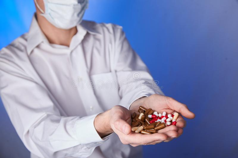 Doctor holds multi-colored pills and pack of different tablet blisters in hands. Panacea, life save service, prescribe medicament,. Legal drug store, disease royalty free stock images