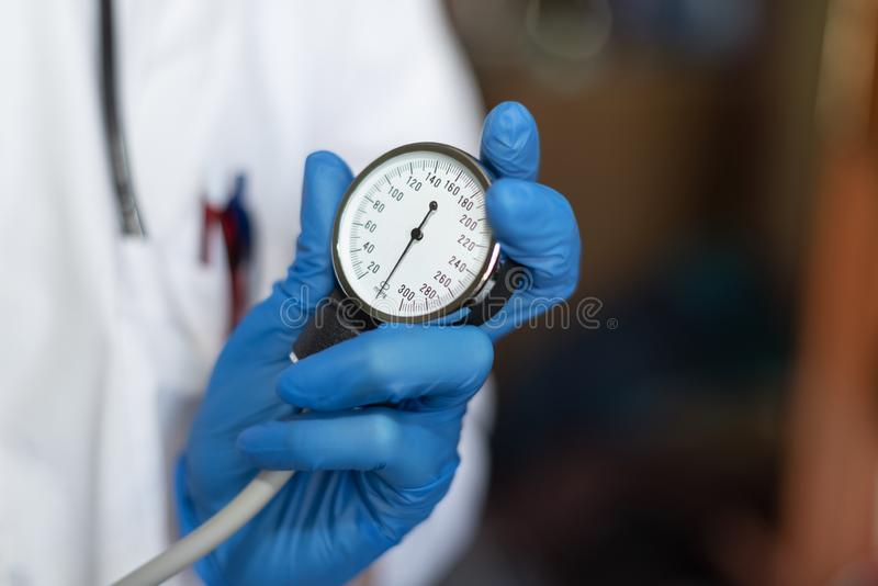 Doctor holds a tonometer for measure of blood pressure. Hand in a blue glove. Sphygmomanometer with phonendoscope royalty free stock image