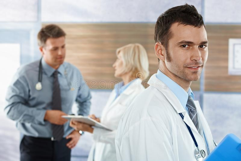 Doctor on hospital corridor. Medical professionals on hospital corridor mid-adult doctor in front looking at camera, smiling stock photos