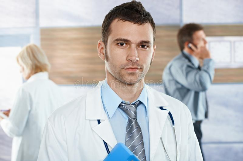 Doctor on hospital corridor. Medical team on hospital corridor mid-adult doctor in front looking at camera, smiling stock images