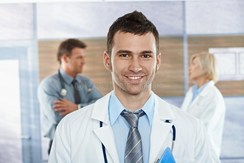 Doctor on hospital corridor. Medical team on hospital corridor mid-adult doctor in front looking at camera, smiling royalty free stock images