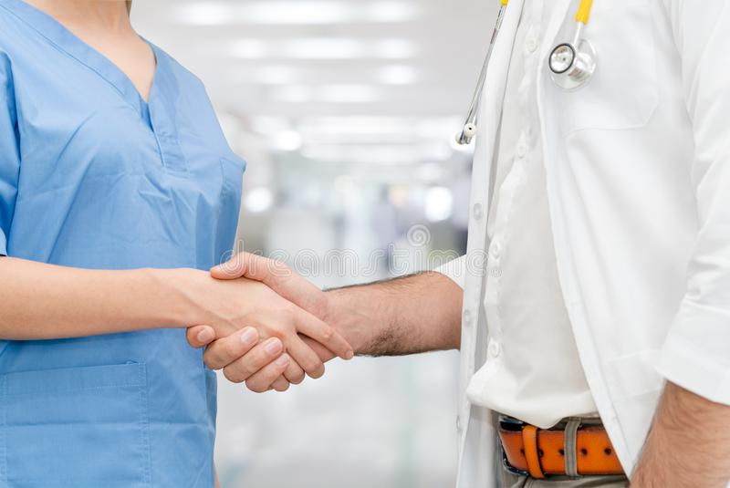 Doctor in hospital handshake with another doctor stock photo