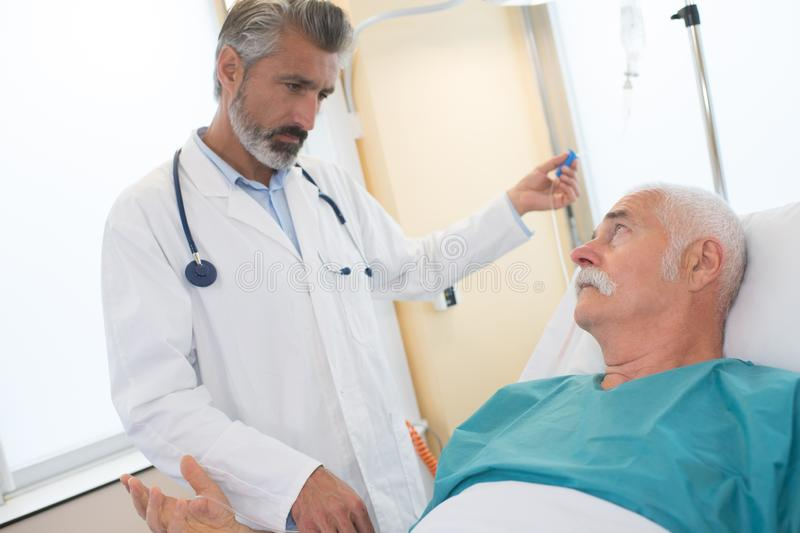 Doctor in hospital room looking at patient royalty free stock photos