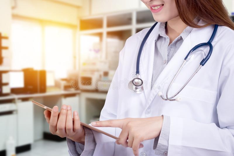 Doctor in hospital working with modern technology for healthy. Close up of friendly doctor with smile pointing at tablet for patient data chart with hospital royalty free stock photography