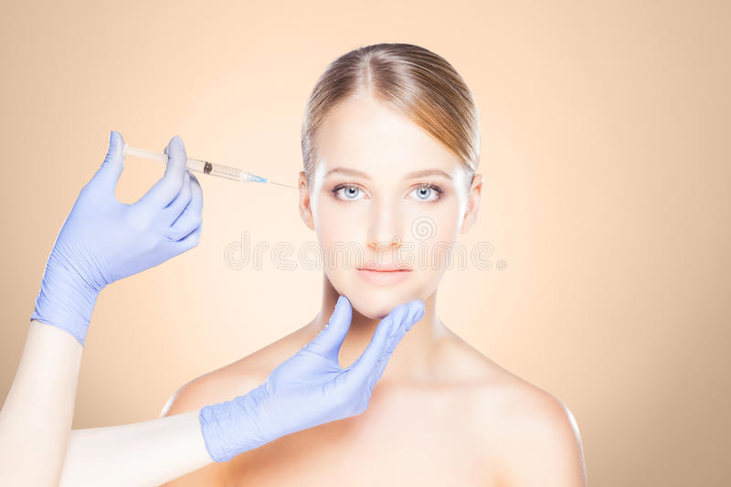 Doctor injecting in a beautiful face of a young woman. Plastic s stock image