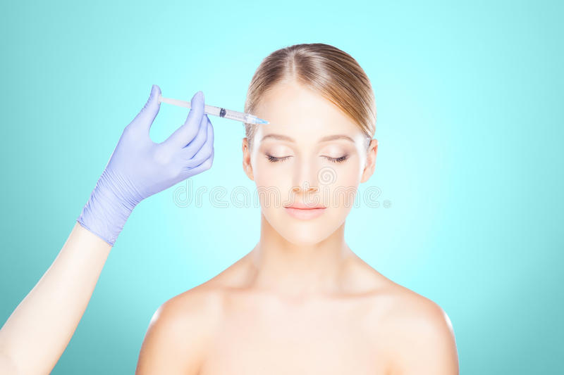 Doctor injecting in a beautiful face of a young woman. Plastic s stock photo