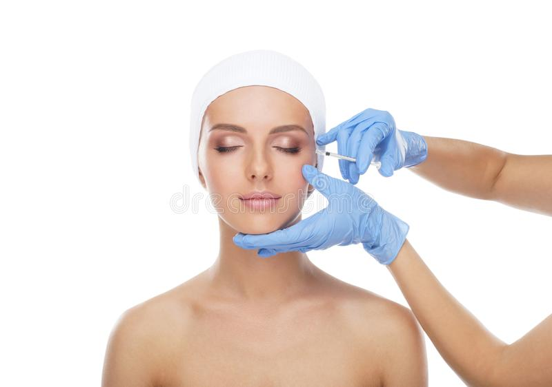 Doctor injecting in a beautiful face of a young woman. Plastic surgery concept. Doctor injecting in a beautiful face of a young woman. Plastic surgery, skin stock photography