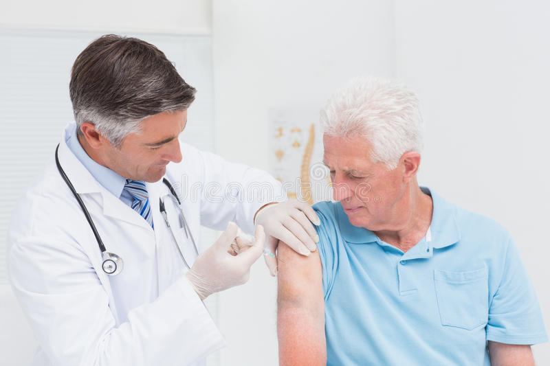 Doctor injecting senior patient in clinic stock images