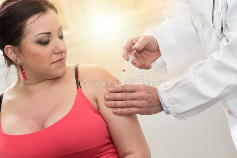Doctor injecting vaccine to young woman, light effect royalty free stock images