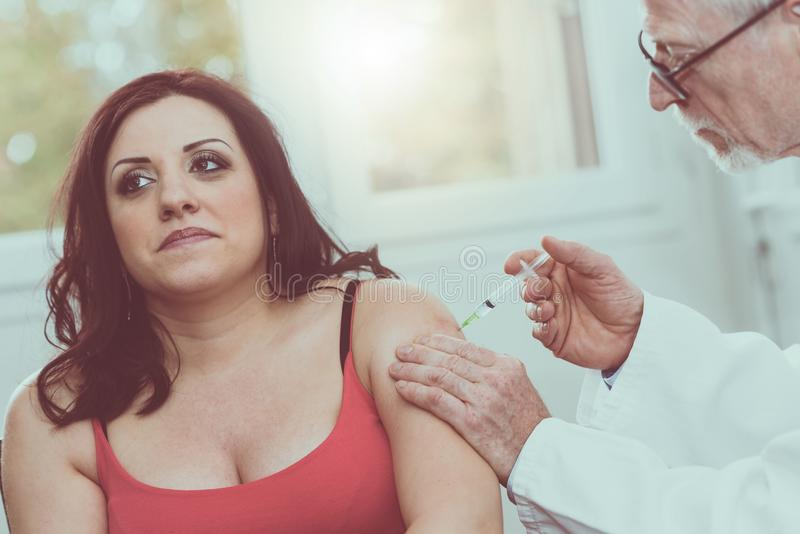 Doctor injecting vaccine to young woman, light effect stock images
