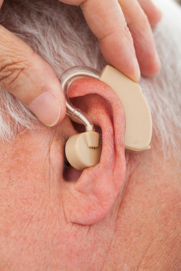 Doctor inserting hearing aid in senior man's ear royalty free stock image
