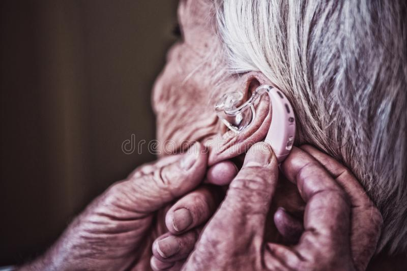 Doctor inserting hearing aid in senior patient ear royalty free stock photos