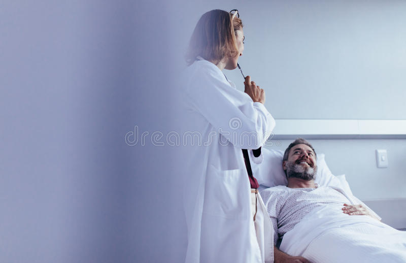 Doctor interacting with patient in hospital ward. Female doctor talking to male patient lying in hospital bed. Medical professional interacting with patient in royalty free stock photography