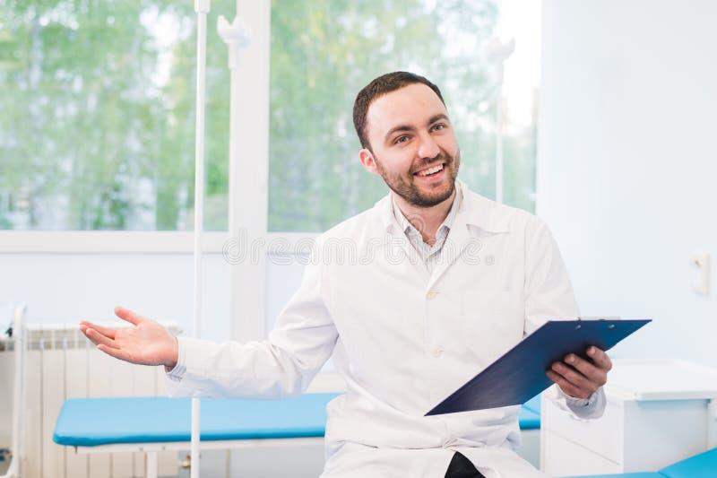 Doctor joven alegre que sostiene un tablero y que gesticula con su mano en la sala de hospital imágenes de archivo libres de regalías