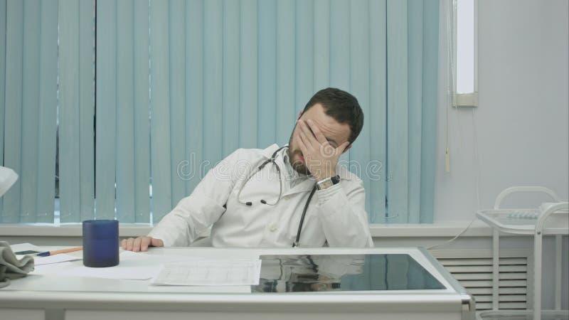 Doctor joven cansado del trabajo, de la mirada en el reloj y de la bebida imágenes de archivo libres de regalías