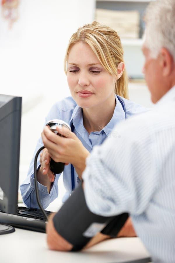 Doctor joven con el paciente mayor foto de archivo libre de regalías