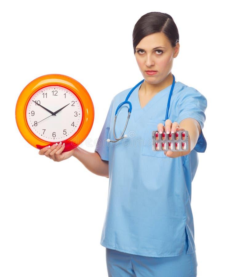 Doctor joven con las píldoras y el reloj fotografía de archivo