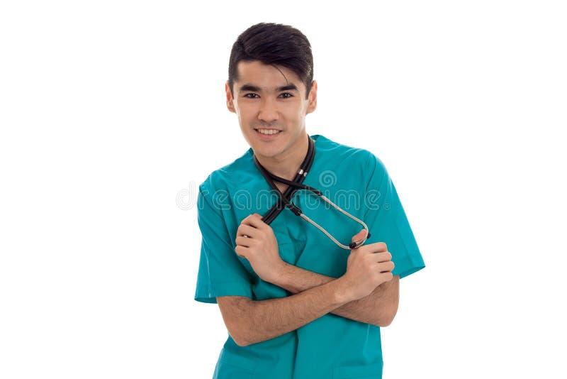 Doctor joven en un traje azul que lleva a cabo el estetoscopio de las manos alrededor de su cuello y miradas fijas en la cámara a imagen de archivo