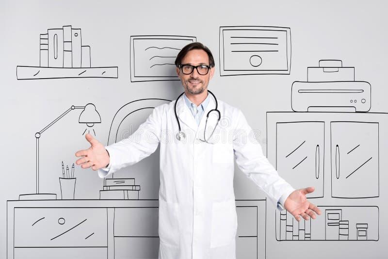 Doctor joven feliz que se coloca en el gabinete foto de archivo