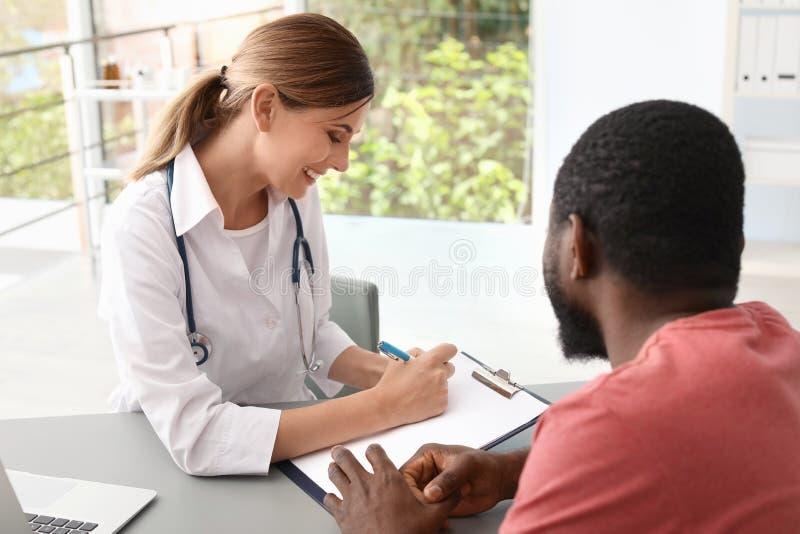 Doctor joven que consulta al paciente afroamericano fotografía de archivo libre de regalías