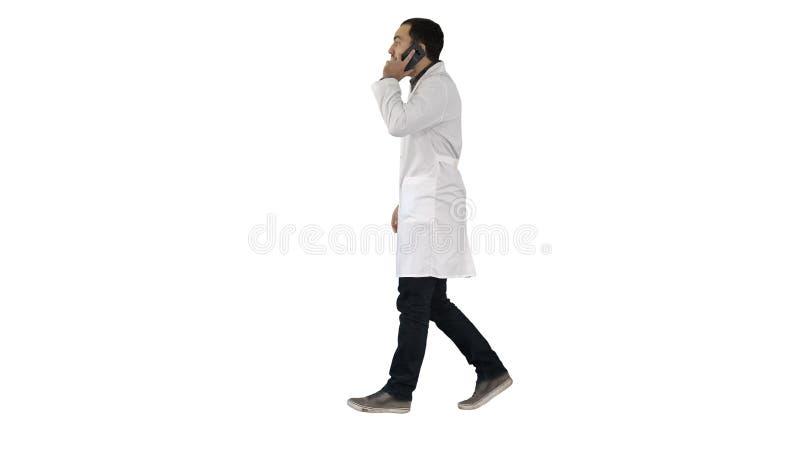 Doctor joven que habla con móvil y el walkind en el fondo blanco foto de archivo libre de regalías