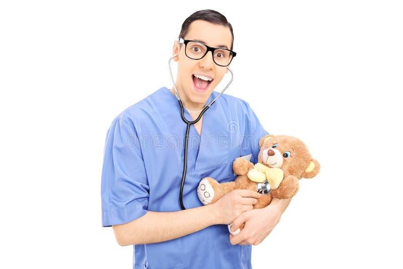 Doctor joven que hace el control médico en un oso de peluche fotos de archivo