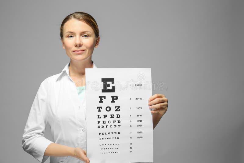 Doctor joven que lleva a cabo la carta de prueba de la vista imágenes de archivo libres de regalías