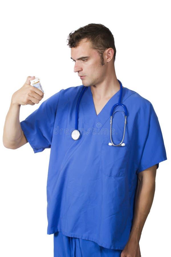 Doctor joven que mira la botella de píldora imagenes de archivo