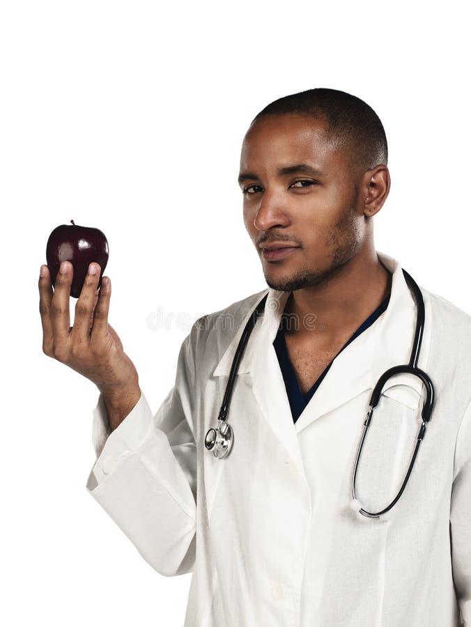 Doctor joven que mira una manzana imagenes de archivo