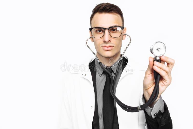 Doctor joven que muestra un estetoscopio a la encuesta Primer, mano imágenes de archivo libres de regalías