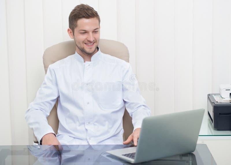 Doctor joven que se sienta en la tabla y que mira la pantalla del ordenador portátil fotos de archivo