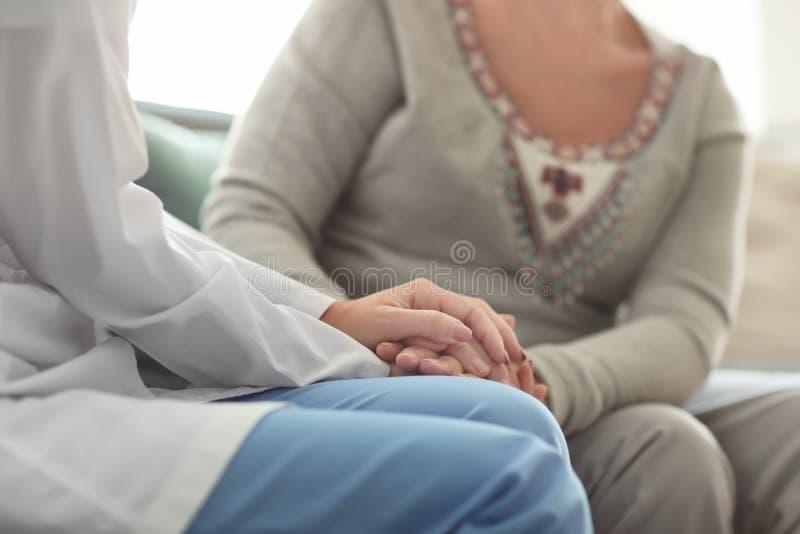 Doctor joven que visita a la mujer mayor en casa imagen de archivo