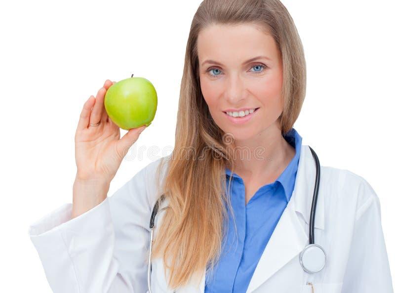 Doctor joven sonriente que da una manzana verde. fotografía de archivo