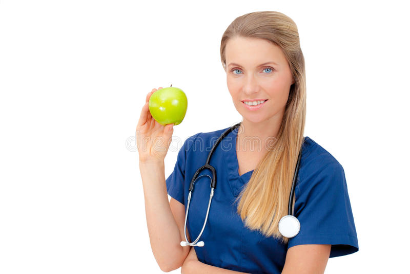 Doctor joven sonriente que da una manzana verde. fotografía de archivo libre de regalías