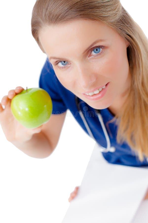 Doctor joven sonriente que da una manzana verde. imágenes de archivo libres de regalías