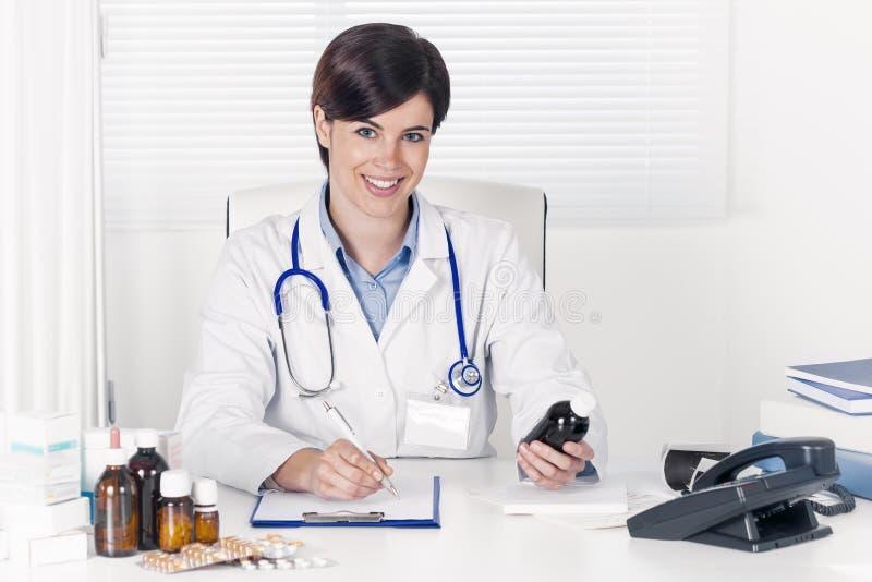 Doctor joven sonriente que pone una prescripción en escrito fotografía de archivo