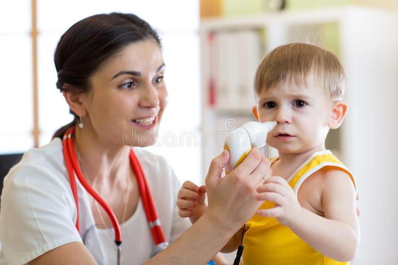Doctor and kid runny nose. Doctor helps to kid with runny nose royalty free stock image