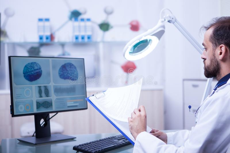 Doctor in laboratory checking the analyzes of a pacient brain after the surgery. Doctor in laboratory control room stock photos