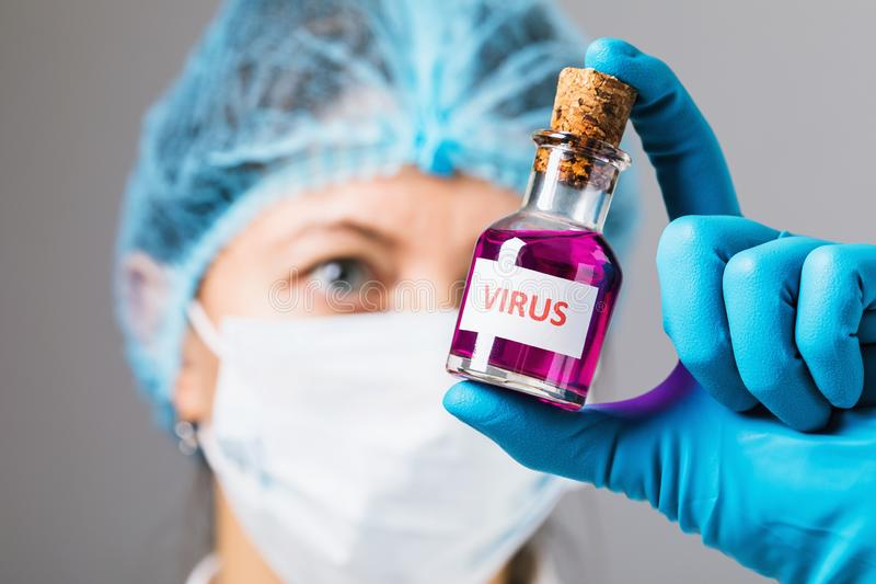 The doctor in the laboratory holds a bottle with the virus in his hands. Concept on the illicit manufacture of toxic substances royalty free stock photography