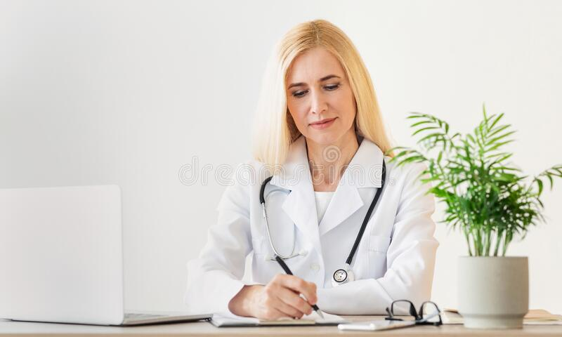 Doctor lady prescribing course of treatment, sitting at workplace royalty free stock images