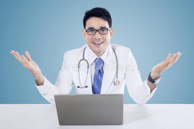 Doctor with laptop and blue background. Male doctor showing welcome gesture with laptop on desk, isolated on blue background stock photography