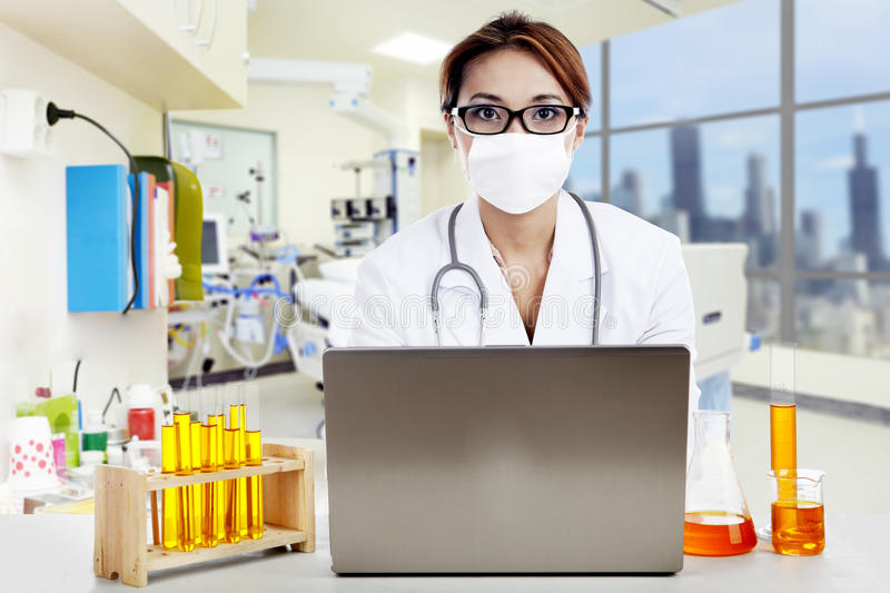 Doctor With Laptop And Flasks Looking At Camera Royalty Free Stock Photos