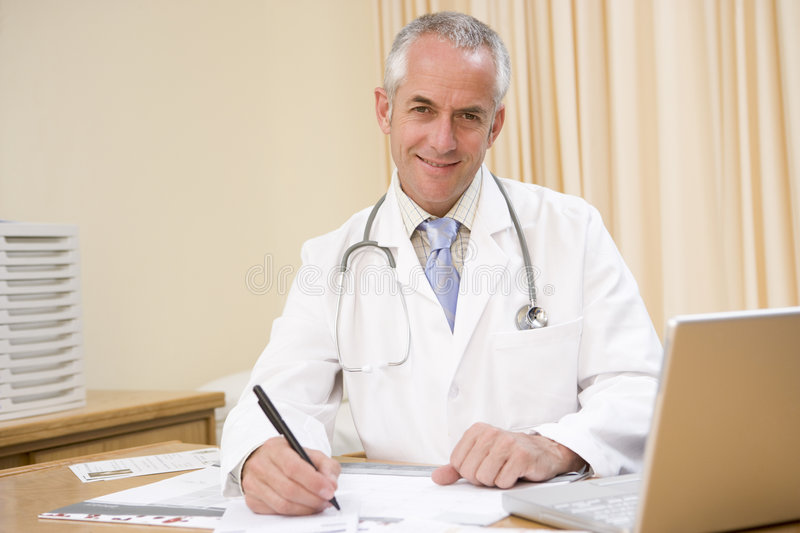 Doctor with laptop writing in doctor s office