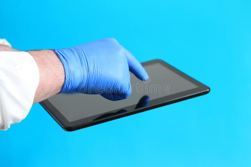 Doctor in latex sterile gloves holding an electronic tablet with a blank black screen royalty free stock photo