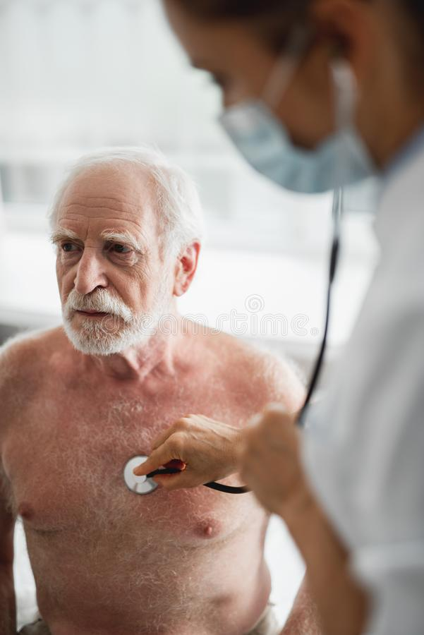 Free Doctor Listening Old Man Breath And Heartbeat With Stethoscope Stock Images - 130115634