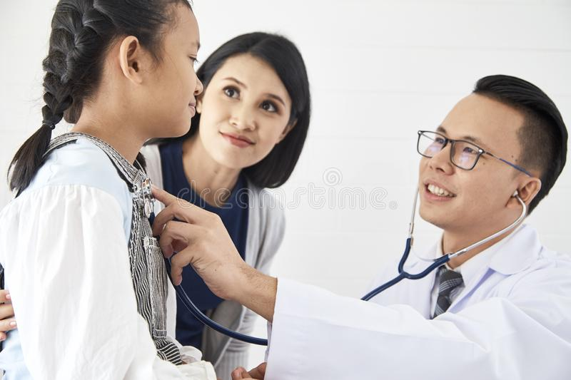 Young woman and her little daughter with pediatrician stock photography