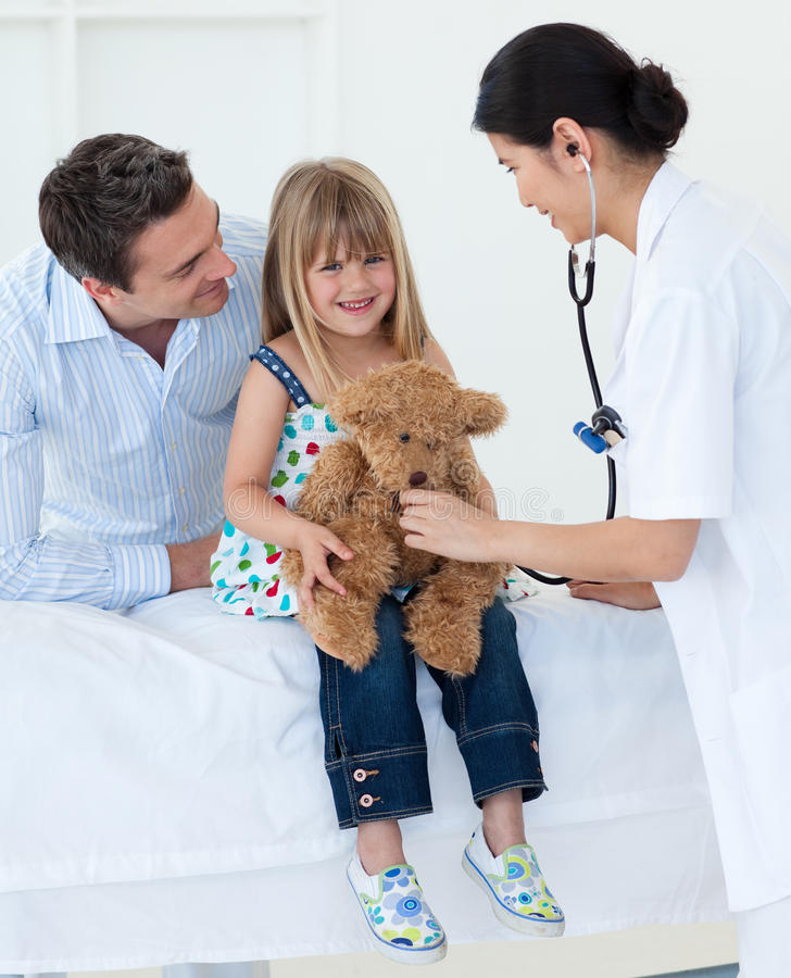 Download Doctor And Little Girl Examining A Teddy Bear Stock Photo - Image: 12011284
